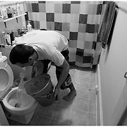 Gabe Albanese uses water from the sink to flush the toilet in the bathroom. He removed a pipe in the sink to catch excess water and uses it to flush the toilet in order to conserve water.