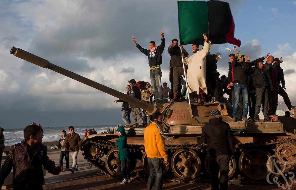 Eastern Libyans celebrate their recent revolution atop a surrendered military tank in the town square of Benghazi Libya February 24, 2011. Pressure continues to mount against Libyan leader Col Muammar el-Qaddafi as a wave of historic and unprecedented uprisings across Libya continue into a second week..Slug: Libya.Credit: Scott Nelson for the New York Times