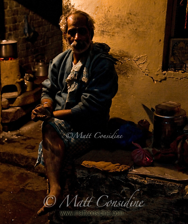 Many people in India carry on much of their normal life outside.  At night there is very little light and as you walk around people suddenly emerge out of the darkness as they live out quiet scenes like this one.<br /> (Photo by Matt Considine - Images of Asia Collection)