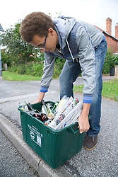 Teenage boy  placing curb side recycling collection box on the pavement ready for collection,