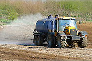 JCB Fastrac tractor towing a water tanker to irrigate a dry field.