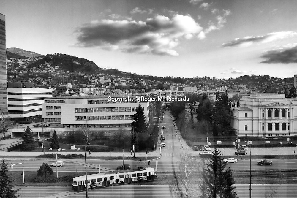 View from a room in the Sarajevo Holiday Inn hotel, facing the hills from which Bosnian Serb forces shelled and sniped at the residents of the city. In the foreground is a tram and cars along Sarajevo's main road infamously known during the siege as 'Sniper Alley'. Photo made on April 1, 2012, almost twenty years to the day when the first shots of the Bosnian war were fired by Serb snipers concealed in the Holiday Inn on peace marchers.