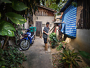 05 JANUARY 2017 - BANGKOK, THAILAND:        A woman sweeps a sidewalk in the Pom Mahakan slum community in Bangkok. More than 40 families still live in the Pom Mahakan Fort community. Bangkok officials are trying to move them out of the fort and community leaders are barricading themselves in the fort. The residents of the historic fort are joined almost every day by community activists from around Bangkok who support their efforts to stay. City officials pushed back their deadline and now say that they expect to have the old fort cleared of residents and construction on the new park started by the end of February 2017.      PHOTO BY JACK KURTZ