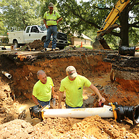 Mike Jackson, bottom left, and Seth Johnson get ready to install to new section of water line along Knight Drive in Saltillo.