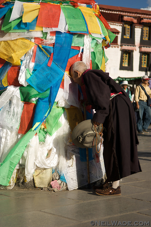 A Tibetan Buddhist pilgrim touches her head to prayer flags as a sign of devotion on Barkor Square in Lhasa, Tibet.