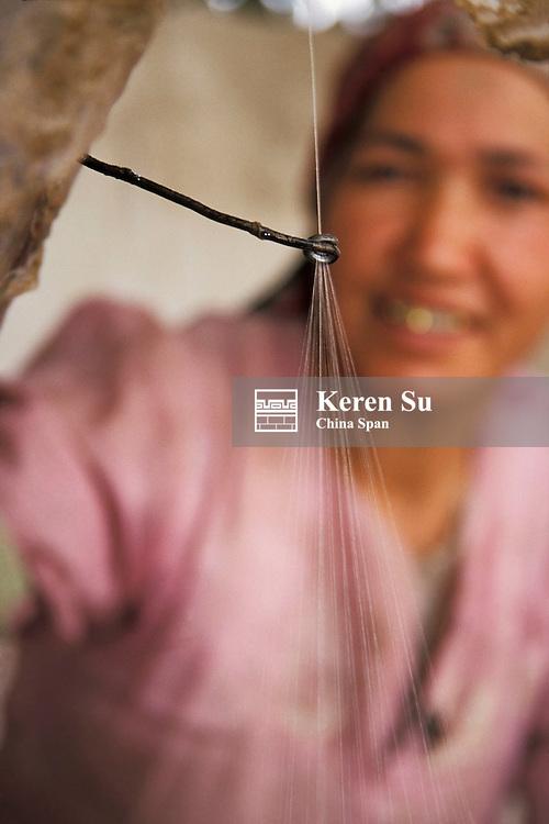 Uighur woman drawing silk thread from the cocoons manually, Hotan, Xinjiang Province, Silk Road, China