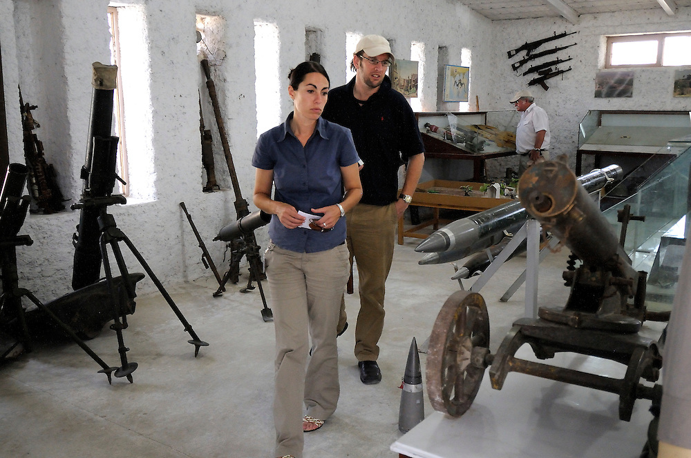 "Pilot, Danielle Aitchison, with partner Chris Hood look at weapons from past conflicts at the OMAR Landmine Museum in Kabul.  Danielle flies in Afghanistan for The United Nations Humanitarian Air Service (UNHAS).   ...When asked about flying in a war zone, she says,  ""I'm just a normal average female.  My job is maybe a little different to some, but I have the same feminine side as other women.  I don't have any trouble going back to New Zealand relating to people.  I'm just a regular chick.""."