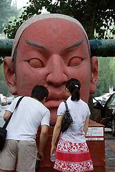 Visitors study large modern art sculpture at 798 Art District  in Beijing