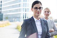 Portrait of confident businesswoman with colleague in background