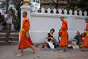 "Mar. 15, 2009 -- LUANG PRABANG, LAOS:  Buddhist Monks in Luang Prabang, Laos, go about their ""Tak Bat,"" Lao for ""monks morning rounds."" The monks collect alms in the form of food from people who line their route. For the monks, it is the only food they get that day, for the people it's a chance to ""make merit."" Luang Prabang is a UNESCO World Heritage Site and the spiritual capital of Laos. There are dozens of ""wats"" or temples and thousands of monks in the city. It is still the center of Buddhist education in Laos. Photo by Jack Kurtz"