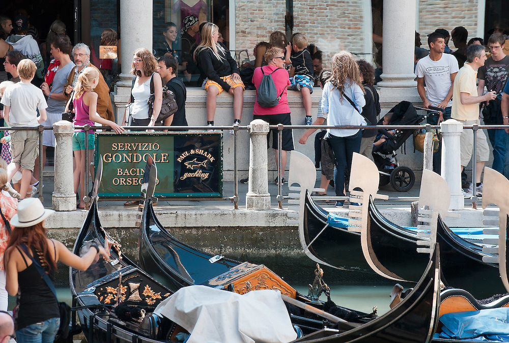 VENICE, ITALY - AUGUST 11:  Tourists walk along Bacino Orseolo near the gondole on August 11, 2011 in Venice, Italy. Italian heritage group Italia Nostra warned  that Venice is facing an irreversible environmental catastrophe unless visitor numbers are capped. The acceptable maximum number of tourists for Venice is 33,000. In 2011 the average number of visitors to the city daily is 60,000 that is too high for such a fragile city and is causing the gradual destruction of the lagoon ecosystem.