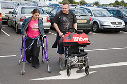 Young couple walking across airport car park about to go on holiday,