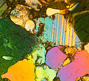 Hornblende crystals, polarized light micrograph. This mineral contains calcium, sodium, magnesium, iron and aluminum in a silicate matrix. It is a member of the amphibole group of minerals, and it is found in igneous and metamorphic rocks. The area here is less than half a centimeter wide.