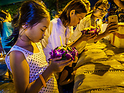 "03 NOVEMBER 2017 - BANGKOK, THAILAND:  A woman uses her smart phone to photograph her daughter praying with her krathong during Loi Krathong near Wat Prayurawongsawat on the Thonburi side of the Chao Phraya River. Loi Krathong is translated as ""to float (Loi) a basket (Krathong)"", and comes from the tradition of making krathong or buoyant, decorated baskets, which are then floated on a river to make merit. On the night of the full moon of the 12th lunar month (usually November), Thais launch their krathong on a river, canal or a pond, making a wish as they do so. Loi Krathong is also celebrated in other Theravada Buddhist countries like Myanmar, where it is called the Tazaungdaing Festival, and Cambodia, where it is called Bon Om Tuk.    PHOTO BY JACK KURTZ"
