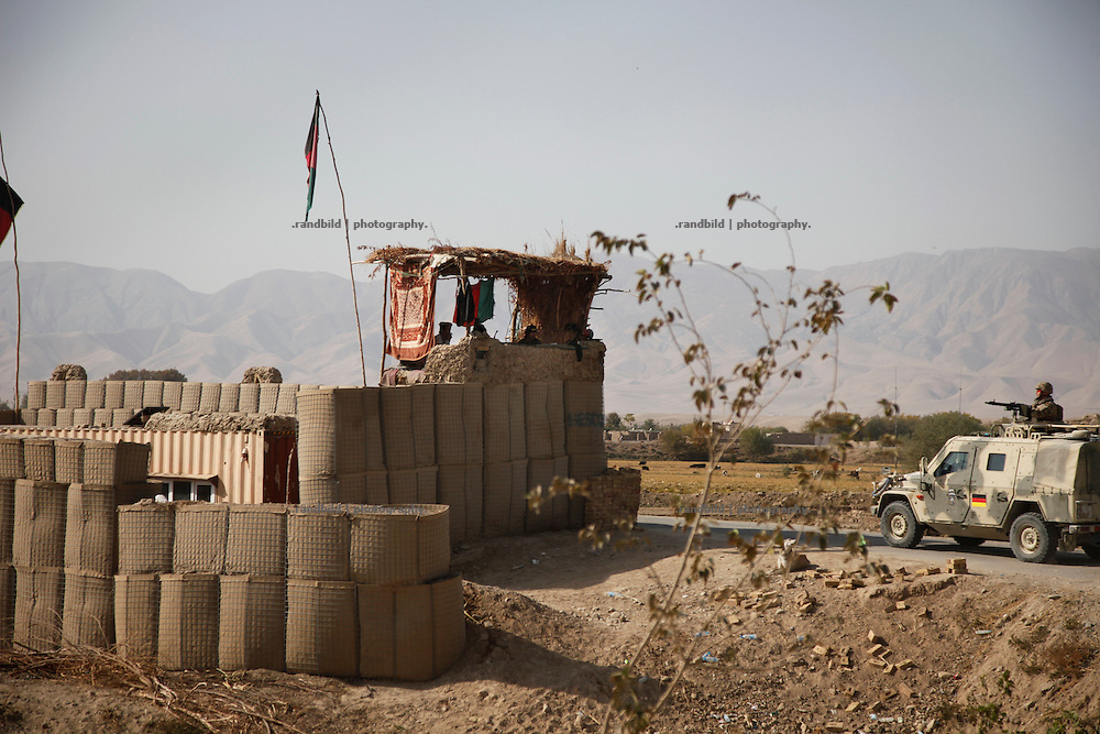 A german pioneer platoon rides out PRT Kunduz on a re-supply mission to the District Headquaters in Chahar Dareh as a jeep passes along a local afghan Combat Outpost at the Mischa-Meier-Bridge.