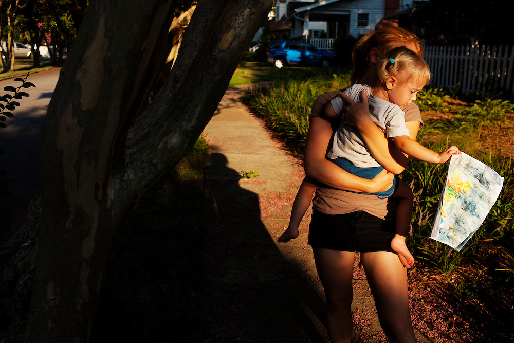 Melissa Eich, 23, and her daughter Madelyn, 2, walk down the sidewalk letting the paint dry after finger painting on the front porch of their home in Norfolk, Virginia on Monday, July 26, 2010.