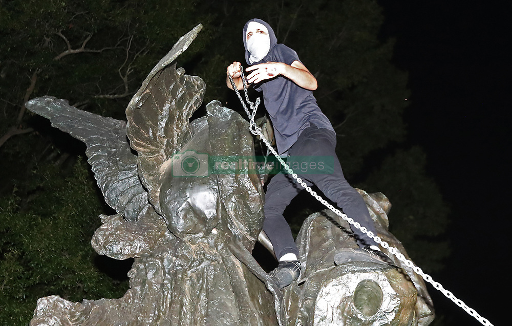 After marching from Woodruff Park to Piedmont Park during a anti white nationalism memorial and march in response to violence in Virginia, a protester climbs a Confederate monument with a chain in an attempt to topple it on Sunday, Aug. 13, 2017, in Atlanta. The peace monument at the 14th Street entrance depicts a angel of peace stilling the hand of a Confederate soldier about to fire his rifle. Photo by Curtis Compton/Atlanta Journal-Constitution/TNS/ABACAPRESS.COM