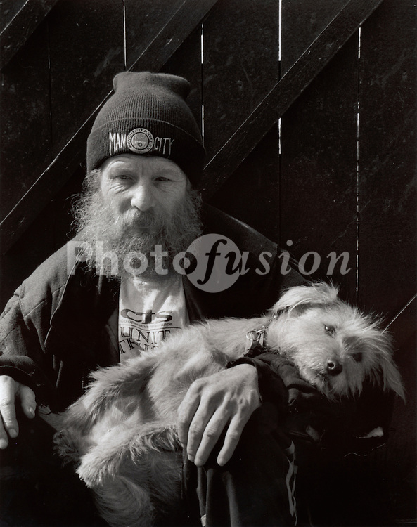 Older homeless man with his dog sitting in the street