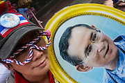 01 FEBRUARY 2014 - BANGKOK, THAILAND: An anti-government protestor holds a portrait of Bhumibol Adulyadej, the King of Thailand. The protestors charge the government of Yingluck Shinawatra doesn't adequately support the monarchy and frequently carry pictures of the King during the protests. The anti-government protest movement, led by the People's Democratic Reform Committee (PDRC) organized a march through the Chinatown district of Bangkok Saturday and disrupted the city's famous Chinese New Year festival. Some streets were blocked and protest leader Suthep Thaugsuban walked through the neighborhood collecting money. The march was in advance of massive protests the PDRC has promised for Sunday, Feb. 2 in an effort to block Thais from voting in the national election.     PHOTO BY JACK KURTZ