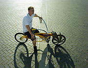 Man sitting on a yellow cruiser bicycle with a big metal marijuana leaf on front wheel.