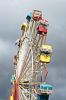 Afternoon sunlight highlights a Ferris wheel against dark gray storm clouds, Blue Hill, Maine.