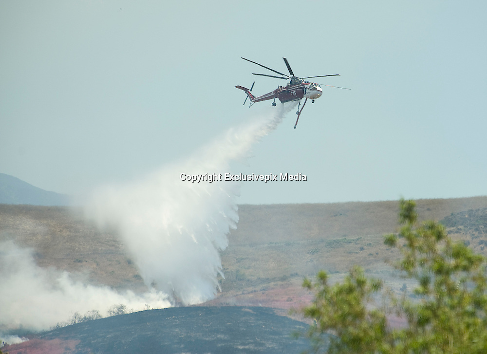 July 13, 2015 - Yorba Linda, CA, USA - <br /> <br /> water planes take to the sky to help put out fires<br /> <br />  A skycrane water dropping helicopter drops a load of water on a vegetation fire that grew to burn more than 100 acres Monday morning, threatened some structures near Irvine Lake and caused officials to close down Santiago Canyon Road in unincorporated Orange County, California<br /> ©Exclusivepix Media