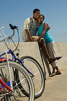 Couple with bicycles embracing on wall