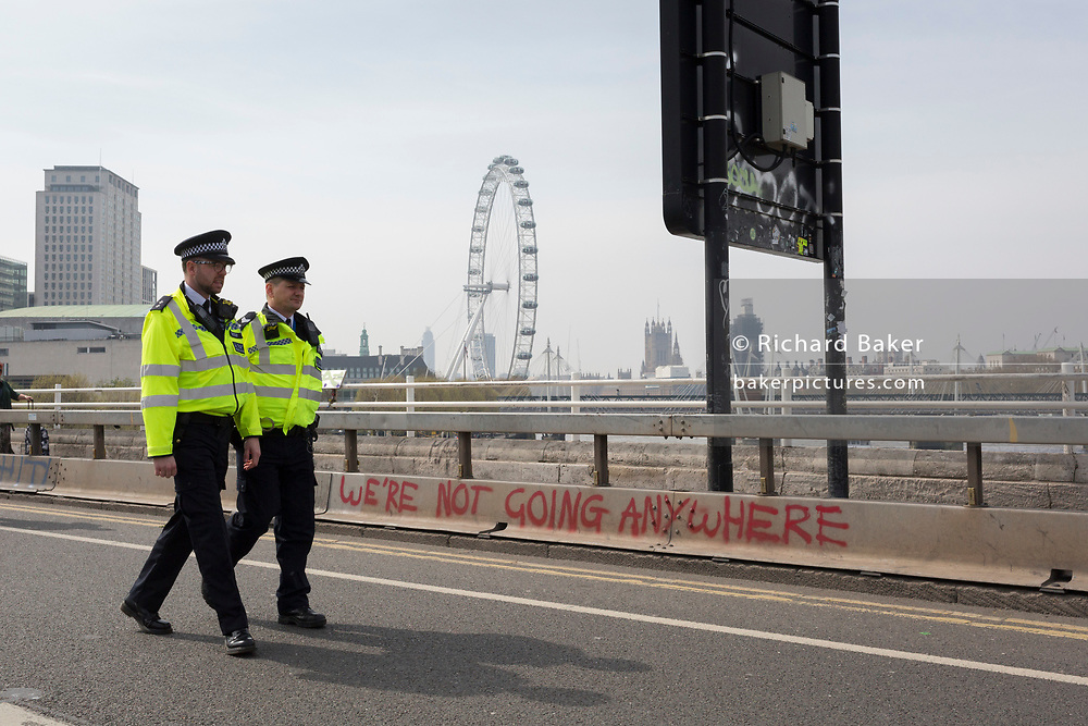 Met police officers walk across the closed Waterloo Bridge on day 4 of protests by climate change environmental activists with pressure group Extinction Rebellion, on18th April 2019, in London, England. The Met have been criticised for allowing the protests to continue their occupations of major roads and junctions such as Waterloo Bridge and Oxford Circus.