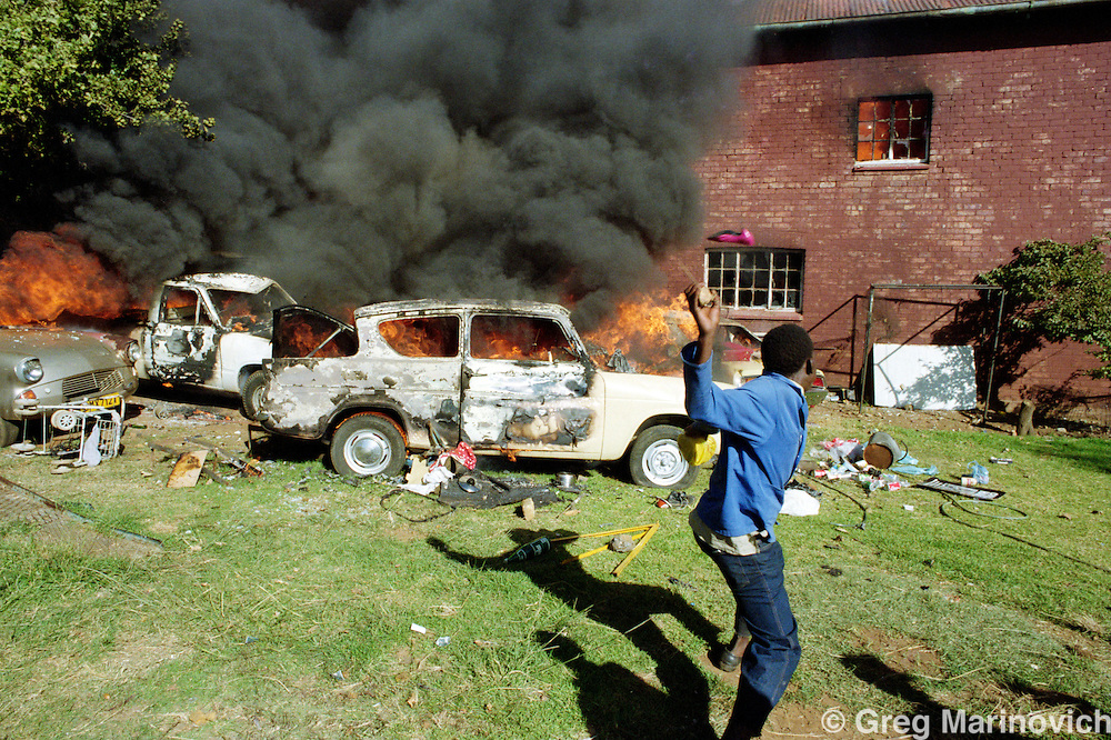 Soweto, South Africa,19 April 1993.  ANC supporters burn cars and a home in which 2 people died outside the Soweto soccer stadium where the funeral for assassinated ANC and SACP leader Chris Hani was being held.
