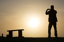 © Licensed to London News Pictures. 23/01/2016.  The photographer stops to capture the morning sun on a mobile phone. Sunrise at Dover in Kent seen from the famous White Cliffs. Weather forecasters have predicted a return to mild weather. Credit : Rob Powell/LNP
