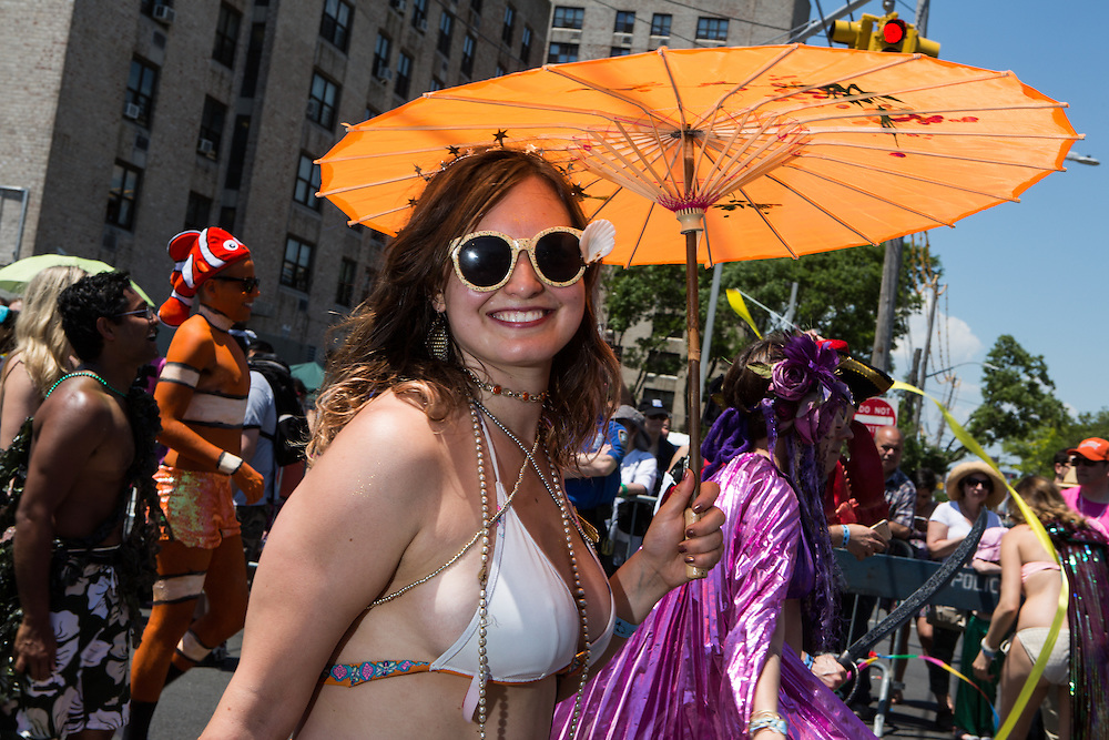 Brooklyn, NY - 18 June 2016. A woman with shell-decorated sunglasses under an orange parasol.