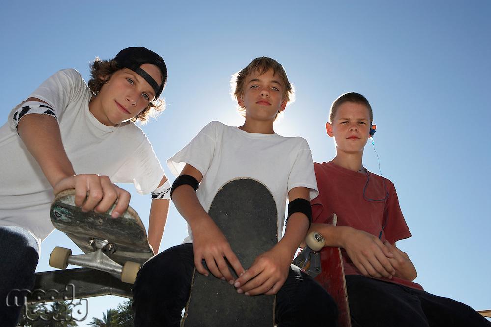 Three teenage boys (16-17) with skateboards outdoors portrait