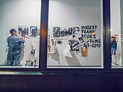 "Portland, Oregon, USA. 26 FEB, 2018. Performance artists mutilate the work of the photographer Robert Frank printed on newsprint in the front window of Blue Sky Gallery in Portland, Oregon, USA. The work was destroyed in a ""Destruction Dance"" performance defacing the photographs with ink and mutilation with scissors, knives and even ice skates  at the end of it's run. The destruction was Frank's protest regarding today's greed in the global art market."