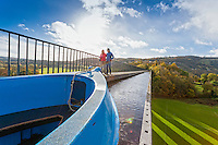 Couple walking on Pontcysyllte Aqueduct in autumn with canal boat passing alongside<br /> Wrexham County<br /> North<br /> Walking<br /> Activities and Sports