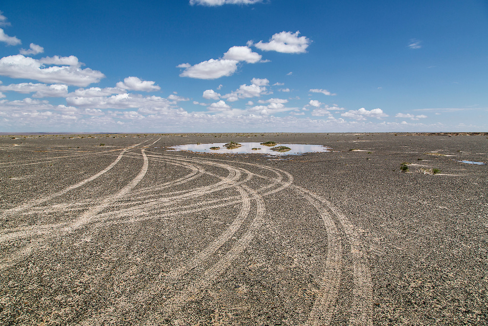 Tracks from a caravan of vehicles are left to mark the landscape on top of a mesa in the Gobi Desert in Mongolia on August 1, 2012. © 2012 Tom Turner Photography