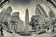 Rockefeller Center, Rockefeller Plaza, from under Saks Fifth Avenue's flags, through fisheye lens, with taxis, bus, and people passing by at street level emphasized, on 5th Ave., Manhattan, NYC, New York, USA, on June 27, 2011. Split tone vintage treatment, full spectrum