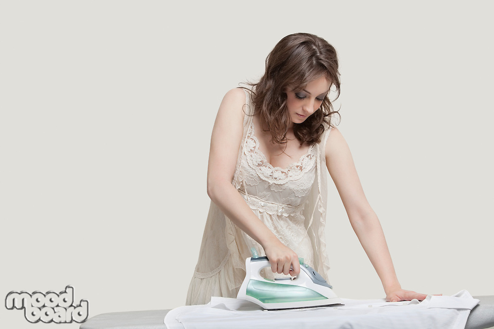Young woman ironing shirt against gray background