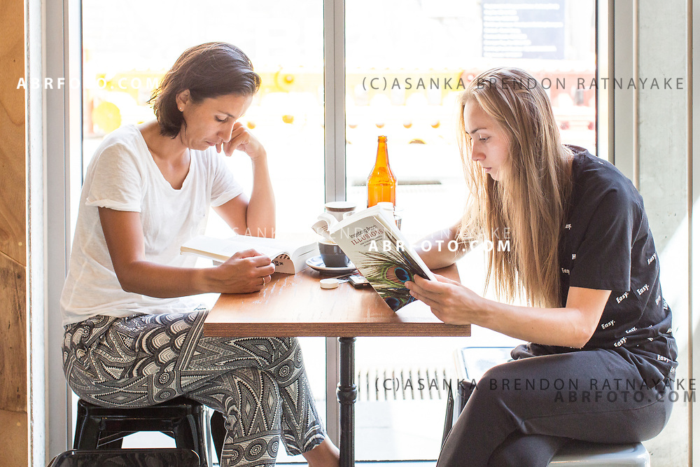 Elise Tamaëla (Left) and Aleksandra Krunić (Right) both reading books at a cafe near their accommodation in Melbourne, Australia on the 11th of January 2018. Asanka Brendon Ratnayake for The New York Times