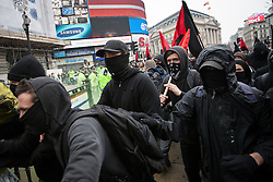 © Licensed to London News Pictures . FILE PHOTO DATED 26/03/2011 of a Black Bloc of protesters in Piccadilly Circus during a demonstration in London as reports circulate that black bloc tactics may be employed by protesters seeking to demonstrate during the funeral of former British Prime Minister Margaret Thatcher . Photo credit : Joel Goodman/LNP