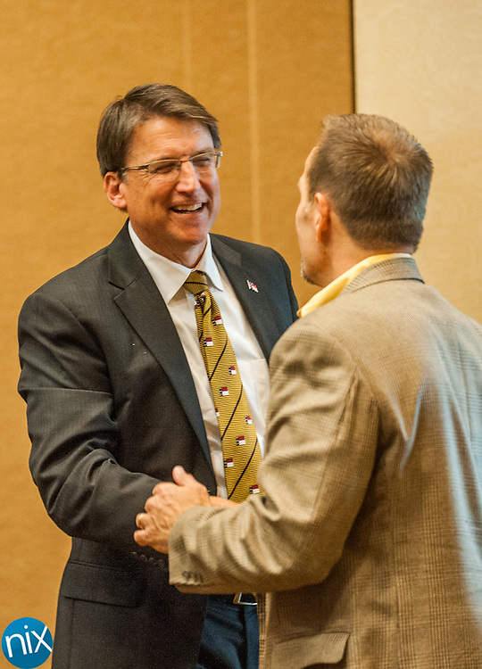 Governor Pat McCrory shakes hands with former Harrisburg Mayor Tim Hagler during a town-hall style meeting at Embassy Suits in Concord Friday afternoon.
