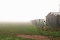 Cottage behind chainlink fence on foggy day