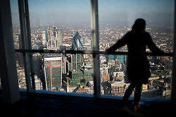 **PICTURES STRICTLY EMBARGOED INTIL 00:01 HOURS FRIDAY 11 JANUARY 2013** © London News Pictures. London, UK.  A woman watches over the London skyline during a media preview of the viewing level of The Shard building in London ahead of the public opening of 'A View From The Shard' on February 1, 2013. The public can view a 360 degree view of the capital from the 72nd floor of Western Europe's tallest building which stands at 800ft (244m).  Photo credit : Ben Cawthra/LNP