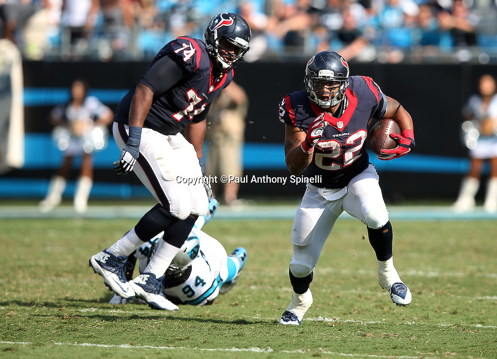 Houston Texans running back Chris Polk (22) works his way up field on a block by Houston Texans tackle Chris Clark (74) on Carolina Panthers defensive end Kony Ealy (94) during the 2015 NFL week 2 regular season football game against the Carolina Panthers on Sunday, Sept. 20, 2015 in Charlotte, N.C. The Panthers won the game 24-17. (©Paul Anthony Spinelli)