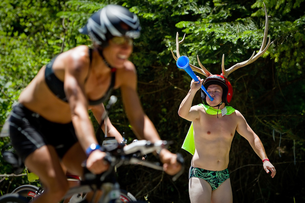 Robby Astin, 19, from Hayden, motivates triathletes with his vuvuzela and his antler helmet as they ascend English Point Road.