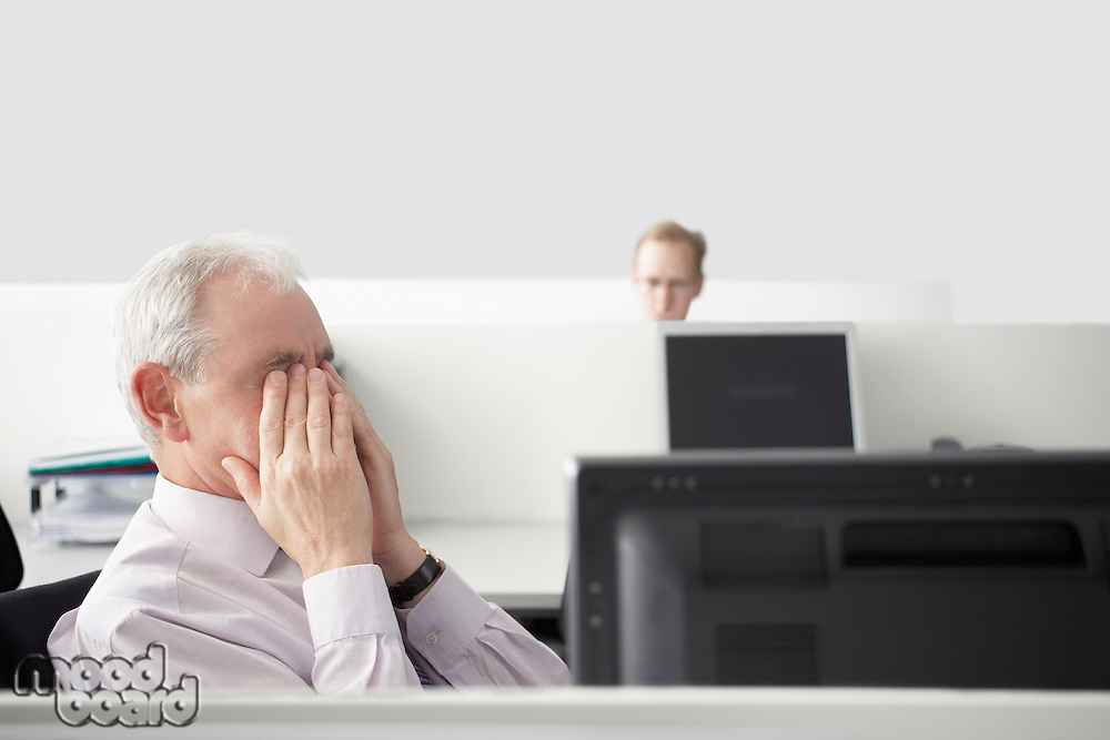 Mature businessman sitting rubbing eyes in office cubicle
