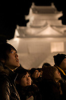 A young couple rugged up against the cold watching a performance at the annual Sapporo Snow Festival held in Odori Park. In the background is a giant ice sculpture of a Japanese castle.