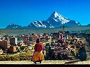 Aymaran Woman Walks Along The Streets Of El Alto, Bolivia With Mt Huayna Potosi Rising In The Background.