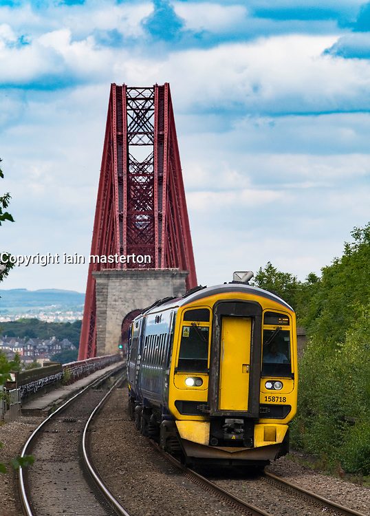 View of Scotrail passenger train approaching Dalmeny Station after crossing Forth Railway Bridge in Lothian , Scotland, United Kingdom.