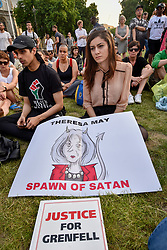 © Licensed to London News Pictures. 19/06/2017. London, UK.  A banner depicting Theresa May is displayed as people gather for a vigil in Parliament Square to remember those who died in the Grenfell Tower fire in North Kensington of 14 June.  Mourners and wellwishers were given the opportunity to speak and to write messages on a community banner.  Photo credit : Stephen Chung/LNP