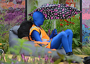 © Licensed to London News Pictures. 02/07/2012. East Molesey, UK. a man in a morph suit shelters from the rain. The RHS Hampton Court Palace Flower Show 2012. The show runs 3-8 July, 2012. Photo credit : Stephen Simpson/LNP
